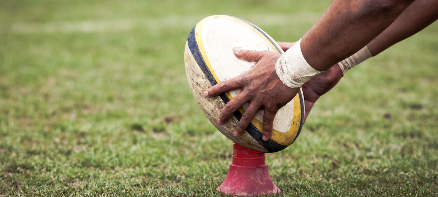 Person placing rugby ball on cone