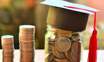 Columns of pennies with jar of pennies wearing graduation cap